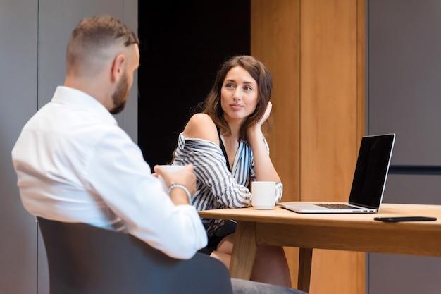 Mooie brunette in gestreept shirt luistert aandachtig naar haar bebaarde partner tijdens werkvergadering op kantoor