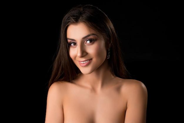 Mooie brunette in het naakt bijgesneden portret tegen zwarte muur