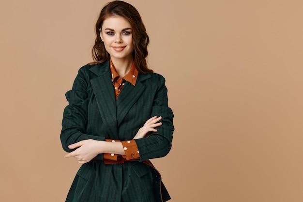 Mooie brunette in jas knuffelen zichzelf met armen en en rood shirt fashion stijl.