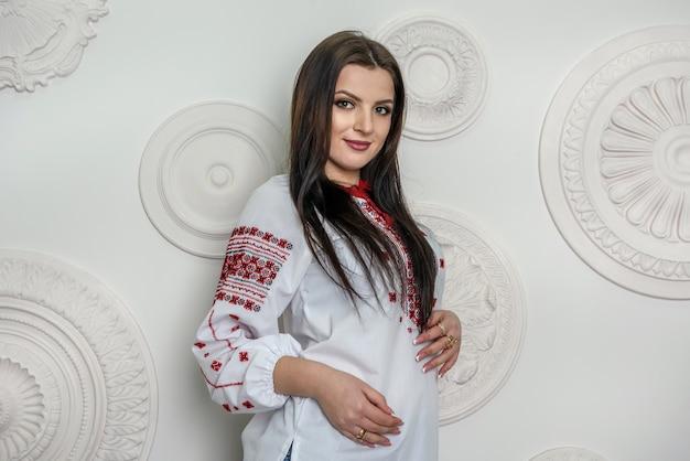 Mooie brunette in traditionele oekraïense blouse poseren in studio