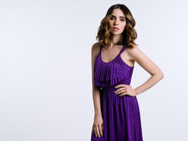 Mooie brunette in violette kleding op lichte achtergrond