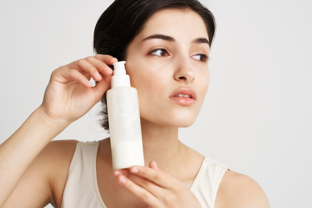 Mooie brunette in witte tanktop crème huid hydraterende cosmetica