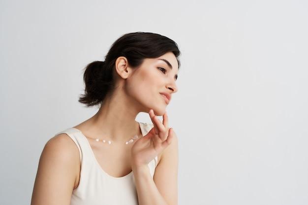 Mooie brunette in witte tanktop crème op gezicht schone huid hydraterend