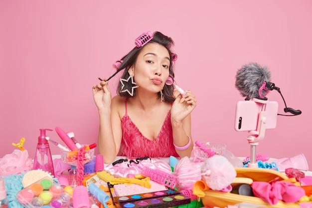 Mooie brunette jonge aziatische dame houdt de lippen gevouwen, brengt lippenstift aan en maakt een kapsel en maakt video-inhoud voor haar kanaal