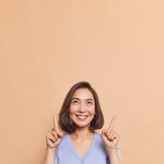 Mooie brunette jonge aziatische vrouw toont kortingswinkelbanner op kopieerruimte, glimlacht zachtjes en geeft opwaartse poses tegen beige muur