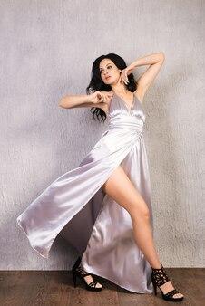 Mooie brunette jonge vrouw in elegante zilveren avondjurk en hoge hakken