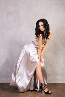 Mooie brunette jonge vrouw poseren in elegante zilveren avondjurk en hoge hakken