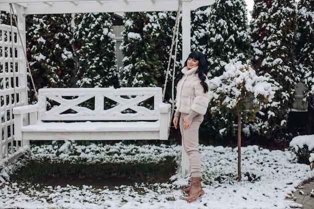 Mooie brunette jonge vrouw warme winterkleren dragen staande in de buurt van tuin schommel buiten in de winter.