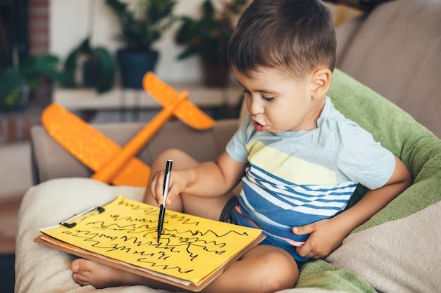 Mooie brunette jongen puttend uit een geel papier met behulp van een marker zittend op kussens thuis
