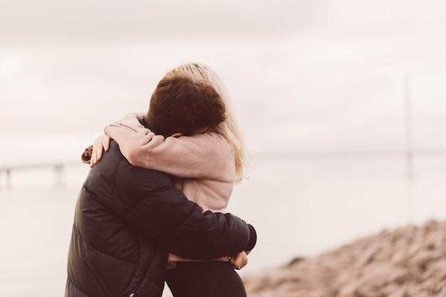 Mooie brunette man en mooie blonde meisje omarmen. liefdevolle tieners zijn blij