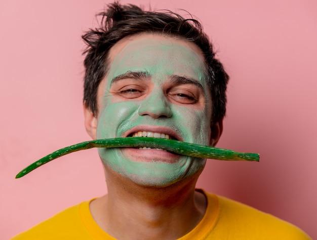 Mooie brunette man met aloë masker op zijn gezicht