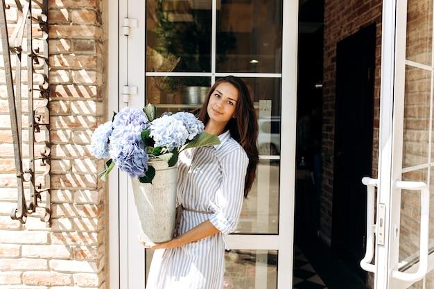 Mooie brunette meisje gekleed in een gestreepte jurk glimlacht en houdt een vaas met lichtblauwe hortensia buiten bij de deur.