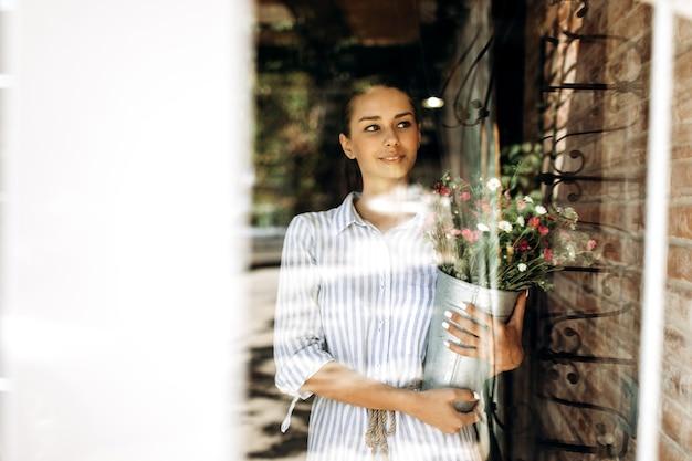 Mooie brunette meisje gekleed in een gestreepte jurk houdt een vaas met roze en witte chrysanten in zonlicht.