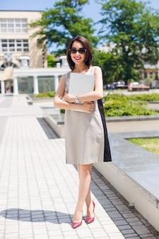 Mooie brunette meisje in grijze jurk en vineuse hakken staat in park in de stad. ze houdt een laptop vast en heeft een vriendelijke glimlach met vineuse lippenstift.