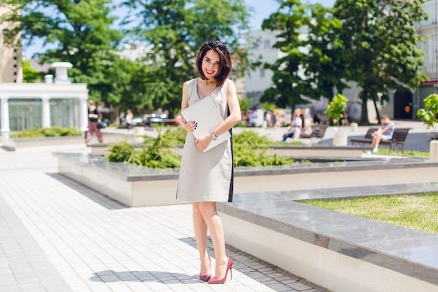Mooie brunette meisje in grijze jurk en vineuse hakken staat in park in de stad. ze houdt een laptop vast en ziet er verlegen uit.