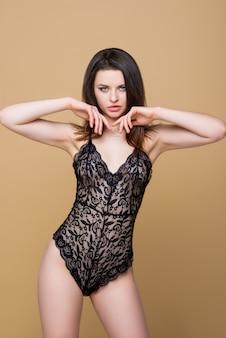 Mooie brunette meisje in sexy zwarte veters combo jumpsuit poseren geïsoleerd op beige achtergrond. mode lingerie. luxe vrouw.