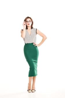 Mooie brunette meisje met bril lichtgroene blouse en strakke rok op een witte achtergrond, trendy make-up, office kleding