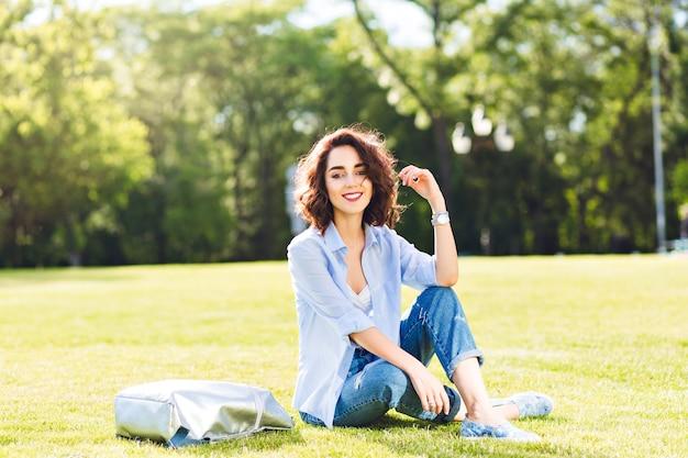 Mooie brunette meisje met kort haar poseren op gras in park. ze draagt een wit t-shirt, overhemd en spijkerbroek, schoenen. ze ziet er gelukkig uit in zonlicht.