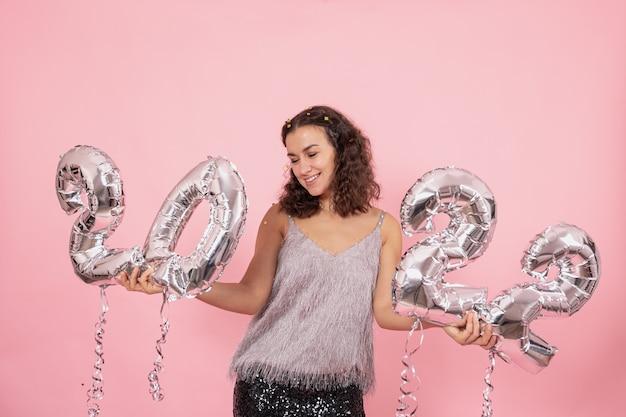 Mooie brunette meisje met krullend haar en feestelijke kleding poseren op een roze achtergrond met confetti en zilveren ballonnen uit de nummers 2022 te houden.