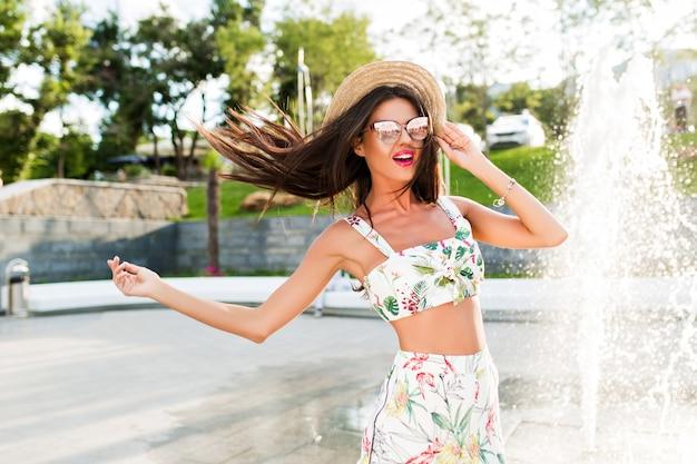 Mooie brunette meisje met lang haar gaat naar de camera in park in de buurt van fonteinen. ze ziet er genoten en gelukkig uit.