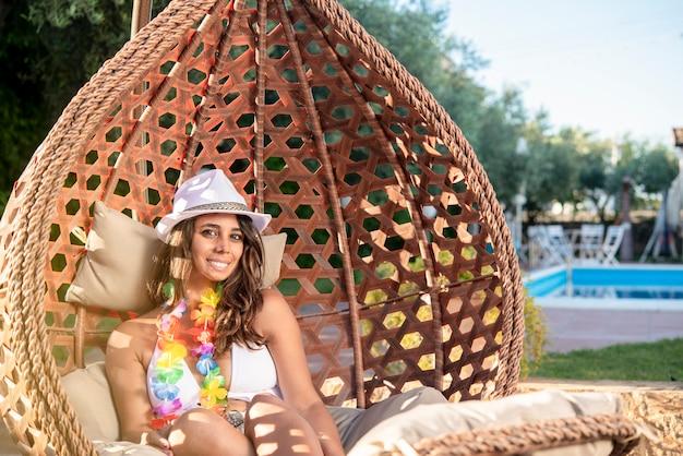 Mooie brunette meisje op een ligstoel glimlacht rustig in een spa in de buurt van een zwembad