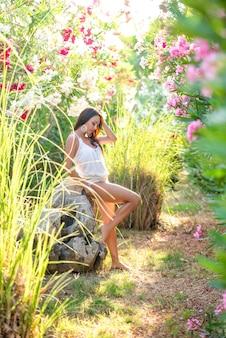 Mooie brunette meisje poseren in de buurt van een steen in een tropische tuin met bloemen.