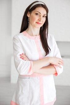 Mooie brunette meisje verpleegster in een wit pak poseren tegen een witte muur achtergrond met gekruiste armen.