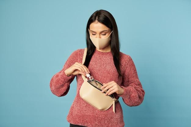 Mooie brunette met een beschermend gezichtsmasker die in de studio poseert en een antisepticum op blauwe achtergrond houdt. ruimte kopiëren. quarantaine, coronavirusconcept