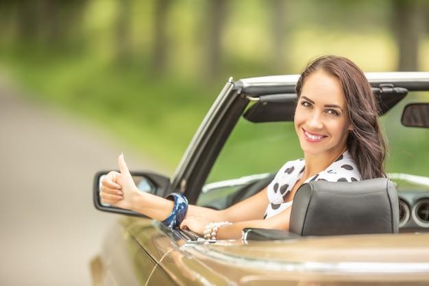 Mooie brunette met een duim omhoog zit in een cabriolet die terug in de camera glimlacht.