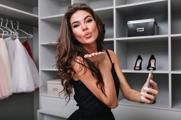 Mooie brunette met lang bruin krullend haar, jong meisje verzenden kus, smartphone in de hand houden. grote mooie kleedkamer. ze stuurt een kus. stijlvolle jurk dragen.
