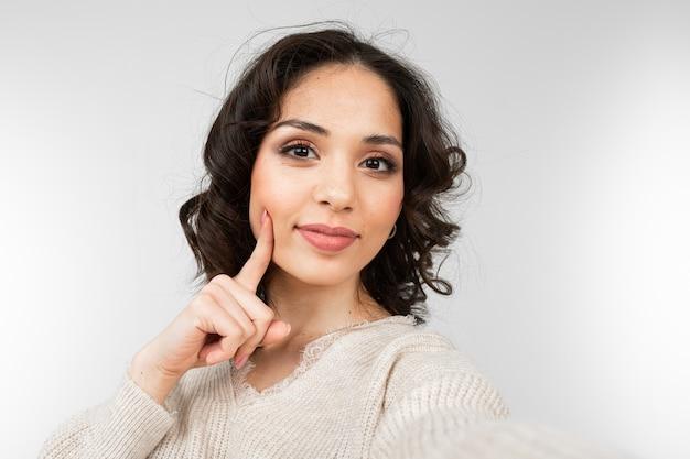 Mooie brunette met make-up meisje selfie te nemen terwijl grimassen