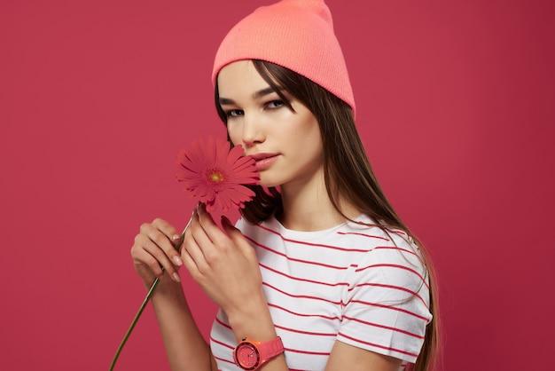 Mooie brunette met roze hoed bloem poseren geïsoleerde achtergrond