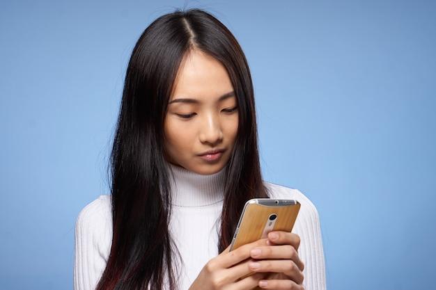 Mooie brunette met telefoon in hand communicatie internettechnologie blauw