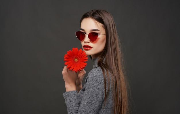 Mooie brunette met zonnebril rode glamour bloem heldere make-up studio