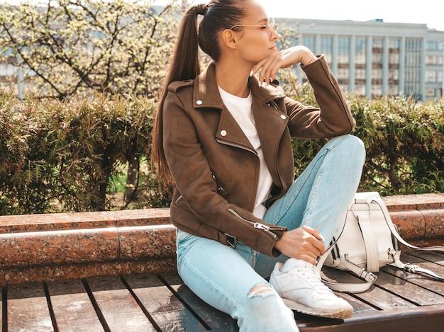 Mooie brunette model gekleed in zomer hipster jas en jeans kleding trendy meisje, zittend op de bank in de straat