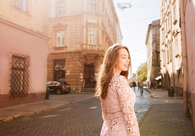Mooie brunette model in kanten jurk poseren met gesloten ogen op de stadsstraat