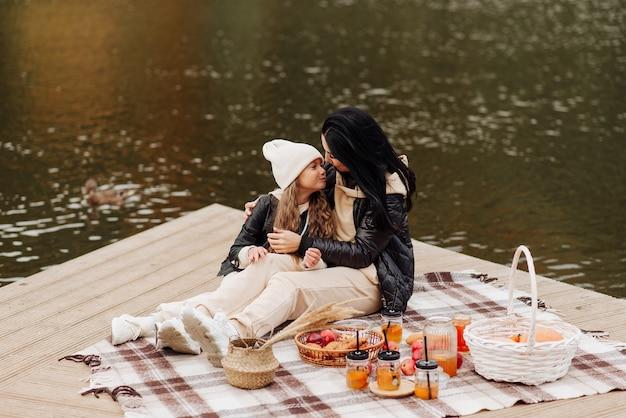 Mooie brunette moeder en haar dochter op een picknick in de buurt van het meer in het herfstpark