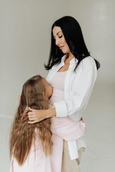 Mooie brunette moeder knuffelt haar dochter met lang blond haar