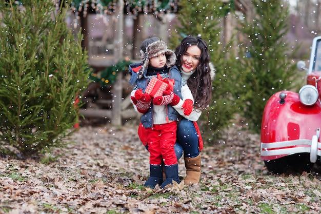 Mooie brunette moeder knuffelt zoon die cadeau te midden van kerstbomen houdt