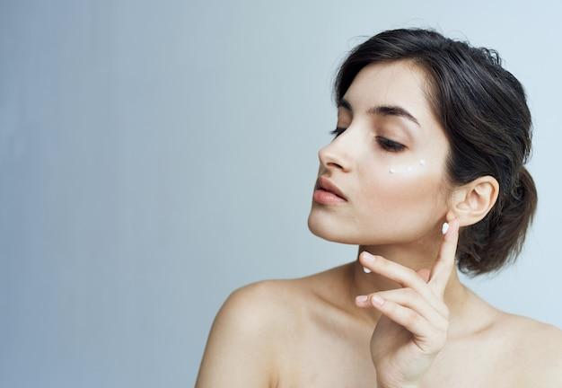 Mooie brunette naakte schouders gezichtshuidverzorging