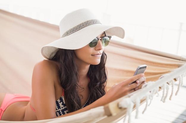 Mooie brunette ontspannen op een hangmat en sms met haar mobiele telefoon