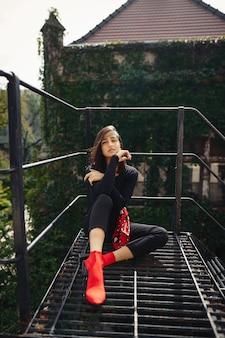 Mooie brunette poseren op een zwarte trap
