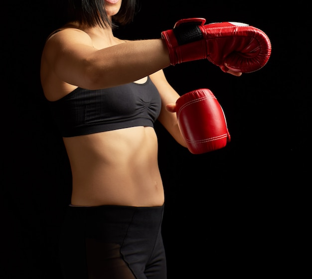 Mooie brunette sportief ogende meisje in een zwarte beha en beenkappen