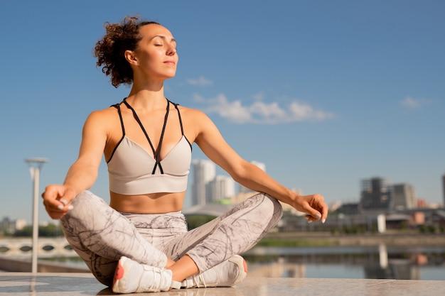Mooie brunette sportvrouw in tanktop en leggins zittend in de pose van lotus op marmeren tegels tijdens het beoefenen van yoga aan de rivier in de ochtend