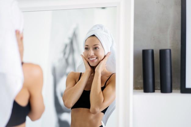 Mooie brunette staat in de badkamer met een handdoek op haar hoofd voor een spiegel
