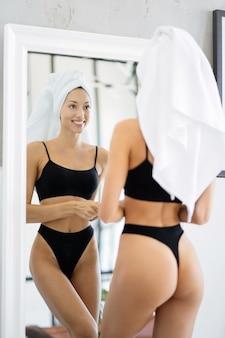 Mooie brunette staat in de badkamer met een handdoek op haar hoofd voor een spiegel.