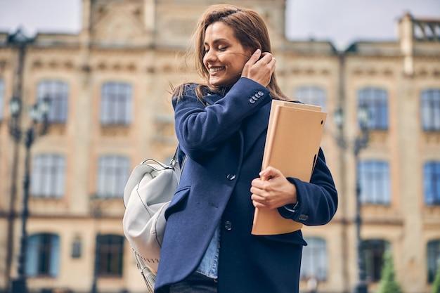 Mooie brunette student met papieren in handen die er gelukkig uitziet terwijl hij bij warm weer in de buurt van een prachtig gebouw staat