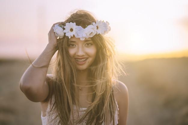 Mooie brunette vrouw die een bloemhoofdband draagt, glimlacht en kijkt naar de voorkant