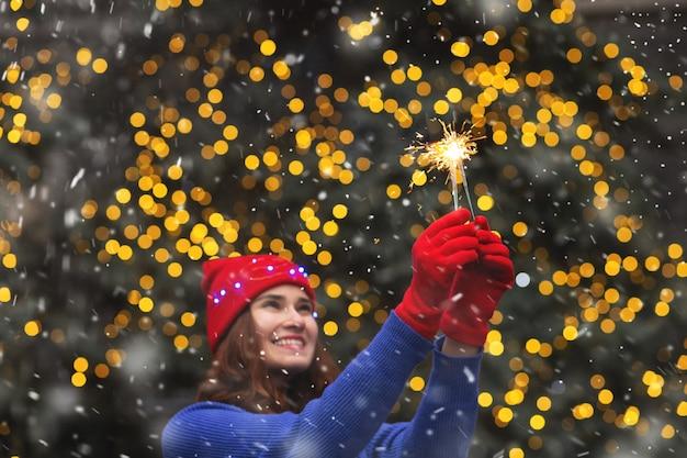 Mooie brunette vrouw die plezier heeft met fonkelende lichtjes tijdens de sneeuwval