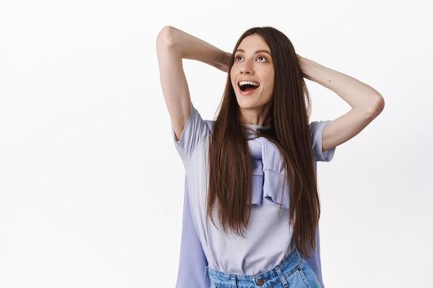Mooie brunette vrouw die vrolijk kijkt in de linkerbovenhoek, rustend met de handen achter het hoofd en lachend, ontspannend, staande over een witte muur